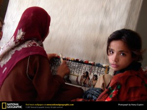 Modern Egyptian woman and girl weaving one of the ancient patterns
