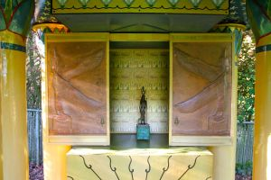 The copper repouse shrine doors slide open so that the standing Isises guard the sacred image within