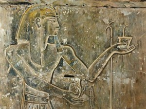 A king offering incense and pouring a libation